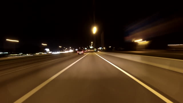 vidéos et rushes de highway freeway expressway road signs city streets passing cars w/ headlights on stopping starting at traffic lights highrise buildings skyscrapers... - rapid city