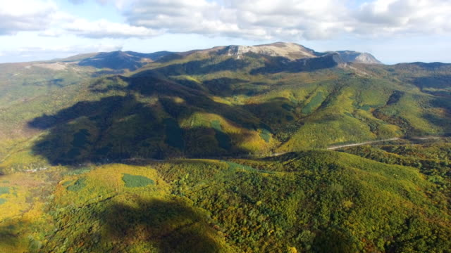 aerial: highway in multi colored mountain forests - chiaroscuro stock videos and b-roll footage