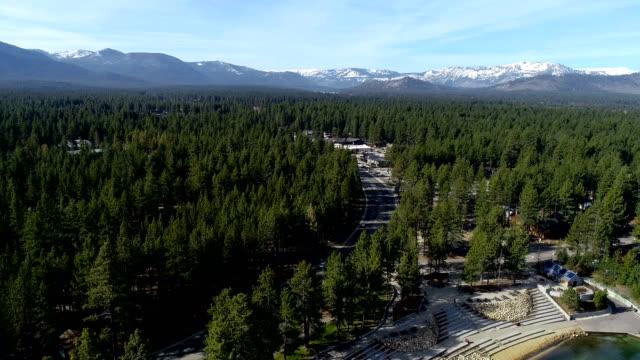 vídeos de stock, filmes e b-roll de rodovia em floresta grossa com fundo de montanhas de neve tampado perto view zangão aéreo de lake tahoe, califórnia movendo-se para fora para mar aberto - moving activity