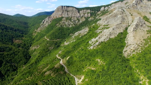 aerial: highway on mountainous wooded slopes - crag stock videos and b-roll footage