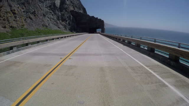 highway one on the pacific coast highway during a sunny day in california with blue sky and some clouds. - route 001 stock videos & royalty-free footage