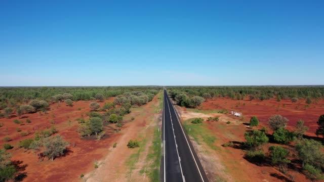 vidéos et rushes de highway, road through semi-arid landscape with red dirt and blue sky, road trip in australia - route déserte