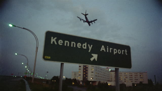 1969 WS LA Highway sign for Kennedy Airport, plane flying overhead, New York City, New York, USA