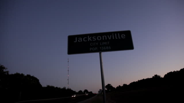 """Highway sign - """"Jacksonville City Limit pop. 13686,"""" at twilight with car headlights passing on the road."""