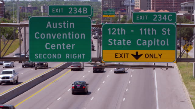 highway signs for the austin convention center and state capitol over interstate 35 - 方向標識点の映像素材/bロール