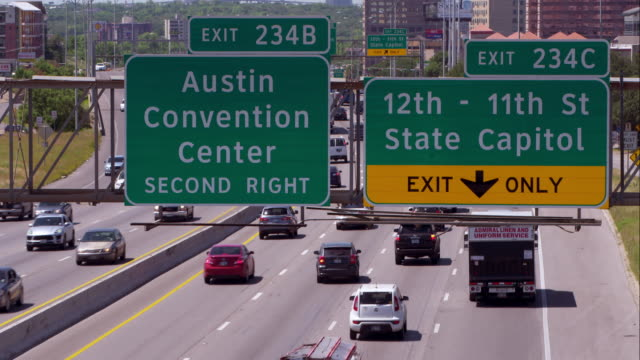 highway signs for the austin convention center and state capitol over interstate 35 - texas stock videos & royalty-free footage