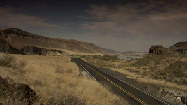 a highway stretches between low mountains and rock formations in the american west. available in hd. - shrubland stock videos & royalty-free footage