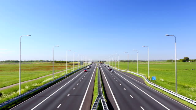 highway through grassy fields on a sunny day, the netherlands - polder stock videos and b-roll footage