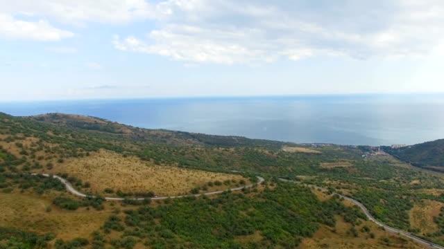 AERIAL: Highway through hilly terrain near blue sea