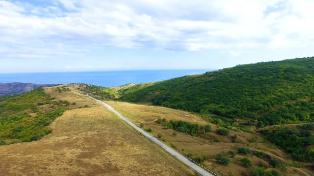 AERIAL: Highway through hilly terrain towards blue sea