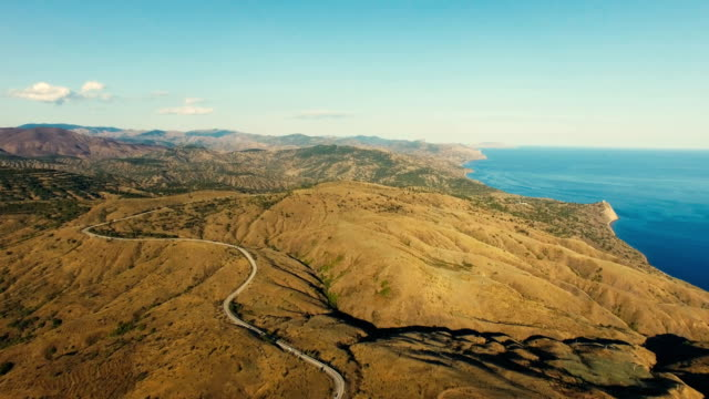 aerial: highway through hilly terrain with distant mountains and blue sea - strada tortuosa video stock e b–roll