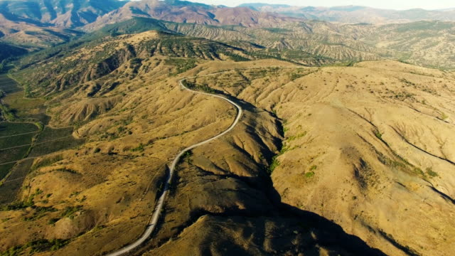 AERIAL: Highway through hilly terrain with distant mountains