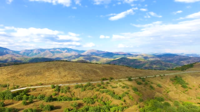 AERIAL: Highway through hilly terrain with distant multi colored mountains