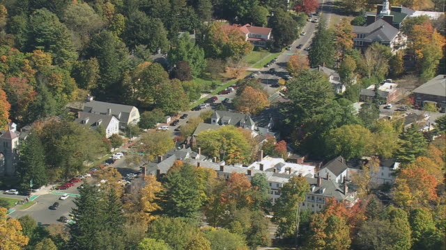 AERIAL Highway through picturesque town dotted with trees changing to fall colors / Massachusetts, United States