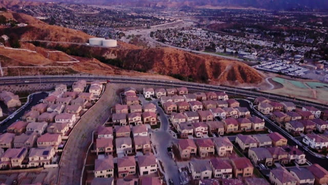 highway through suburbia - aerial view - tract housing stock videos & royalty-free footage