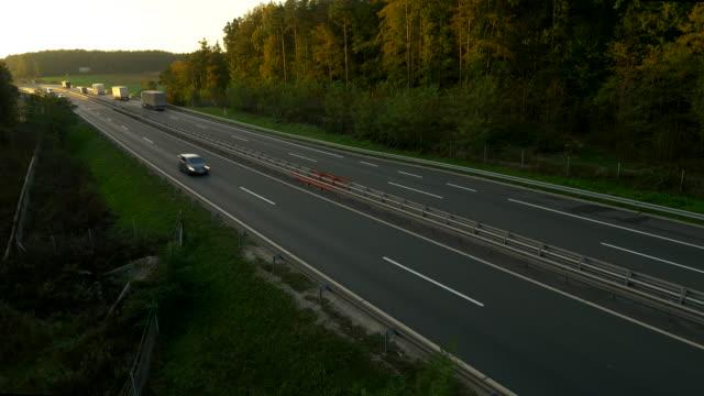 vídeos de stock, filmes e b-roll de vista aérea estrada através da zona rural - pista asfaltada