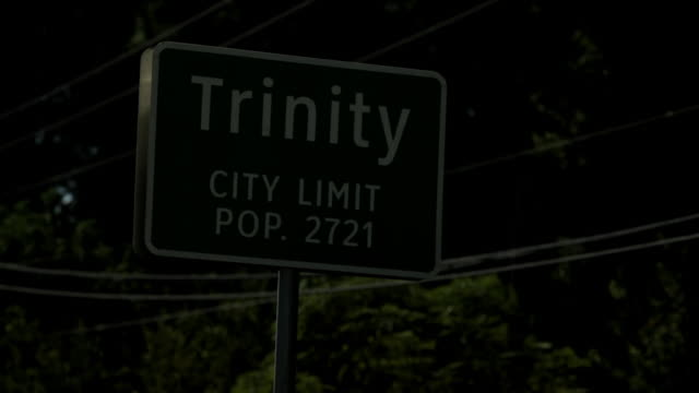 """Highway town sign at night, which reads, """"Trinity City Limit pop. 2721"""""""