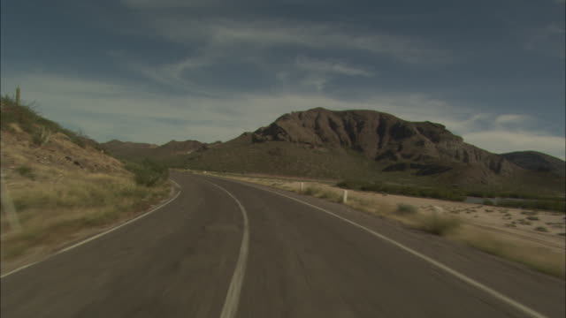 a highway winds through a desert. - cactus stock videos & royalty-free footage