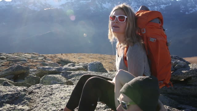 Hiker and companion have conversation while relaxing, mtns