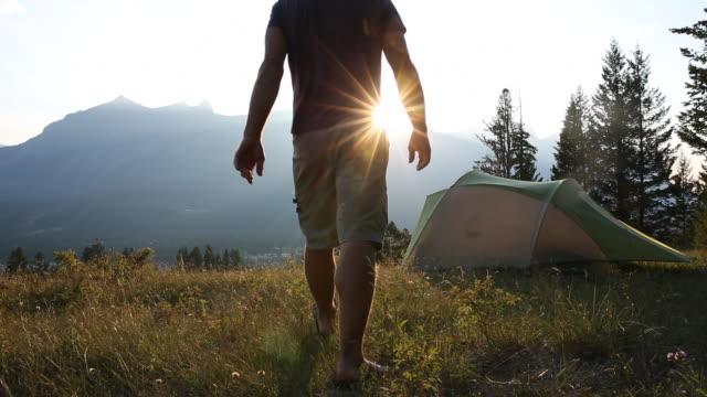 hiker approaches tent, looks towards mountains, sunrise - zelt stock-videos und b-roll-filmmaterial