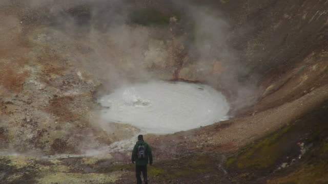 ms ha hiker approaching steaming geyser / iceland - geyser video stock e b–roll
