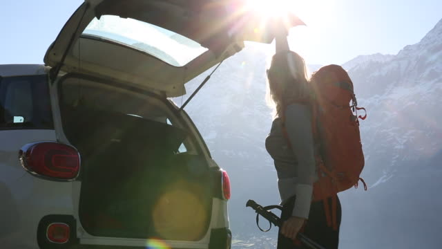 hiker arranges gear, looks off to mountain view, from roadside - roadside stock videos & royalty-free footage
