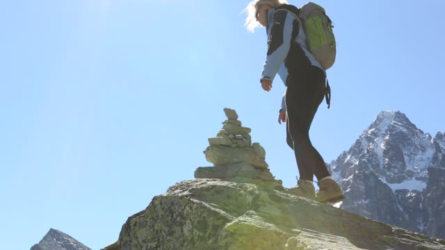 Hiker arrives at mtn summit, is joined by companion