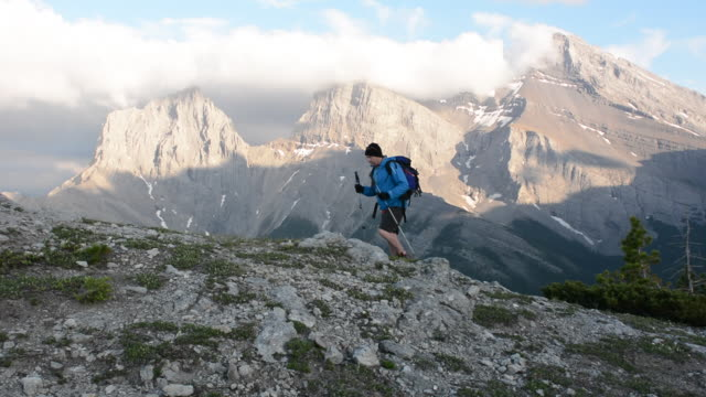 vidéos et rushes de hiker ascends mountain ridge to summit, extends arm - un seul homme d'âge moyen