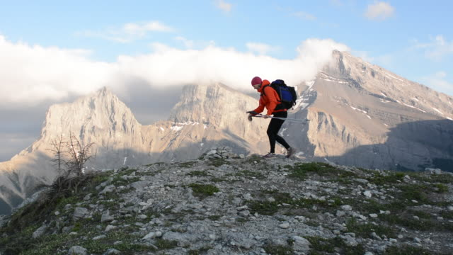 Hiker ascends mountain ridge to summit, extends arms