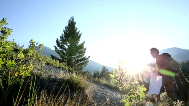 Hiking-Schuh führt Berghang bei Sonnenaufgang, sieht in Karte