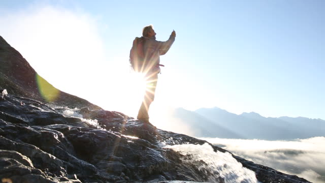 Hiker ascends rock ridge, above mountains, fog