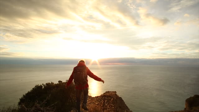 Hiker ascends to cliff edge, looks out to sea, sunrise