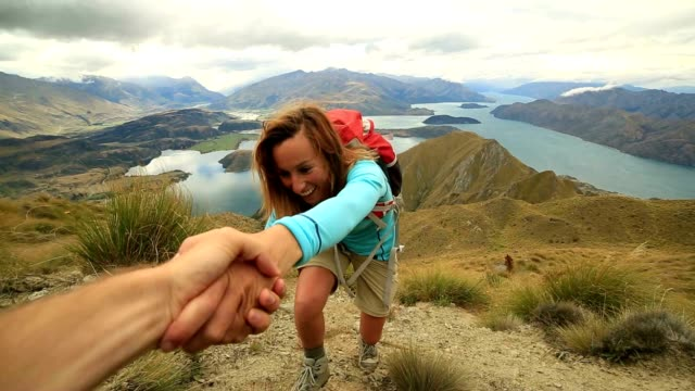 hiker assists teammate on mountain top - reaching stock videos & royalty-free footage