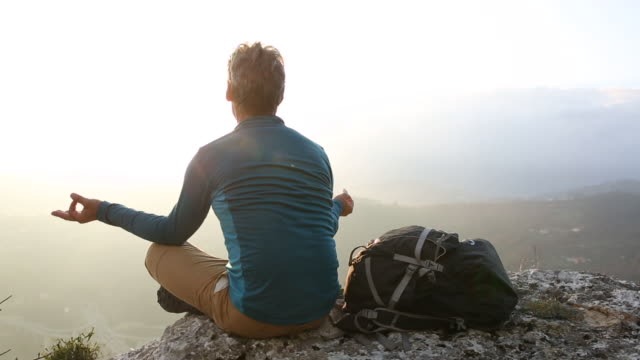 Hiker assumes yoga stance, looks out across hills