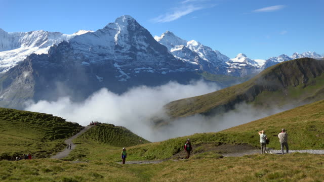 hiker at grindelwald-first with eiger and jungfrau, bernese alps, switzerland, europe - bernese alps stock videos & royalty-free footage