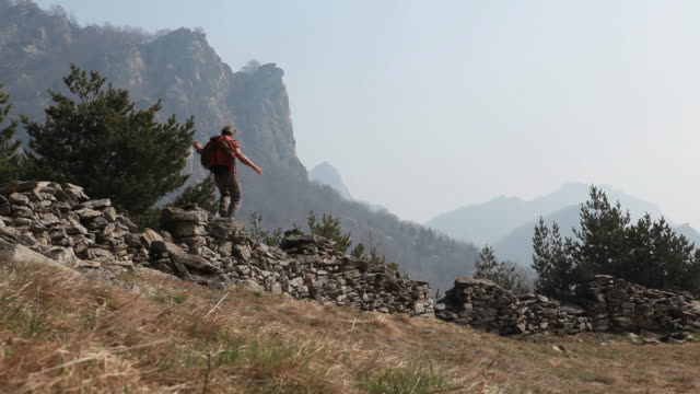 hiker balances on stone wall, above mtn meadow - stone wall stock videos and b-roll footage