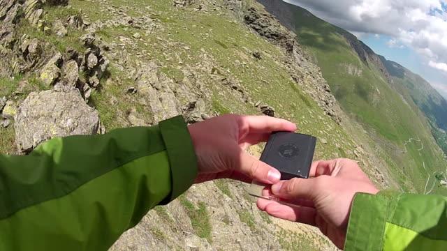 POV of hiker checking compass on ridge crest