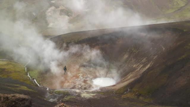 ms ha hiker climbing near from steaming geyser / iceland - geyser video stock e b–roll