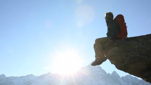 Hiker climbs to mountain summit, then relaxes on top