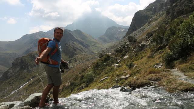 Hiker crosses mtn creek, offers hand to companion