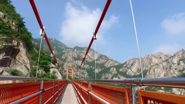 pov hiker crossing cloud bridge over wolchulsan mountain in yeongamgun, jeollanam-do, south korea - jeollanam do stock videos & royalty-free footage