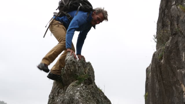 Hiker descends from rock platform above hills, sunrise