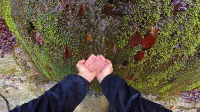 vídeos y material grabado en eventos de stock de hiker drinking water from personal point of view of a waterfall in the mountain region of garrotxa of catalonia. - manos ahuecadas