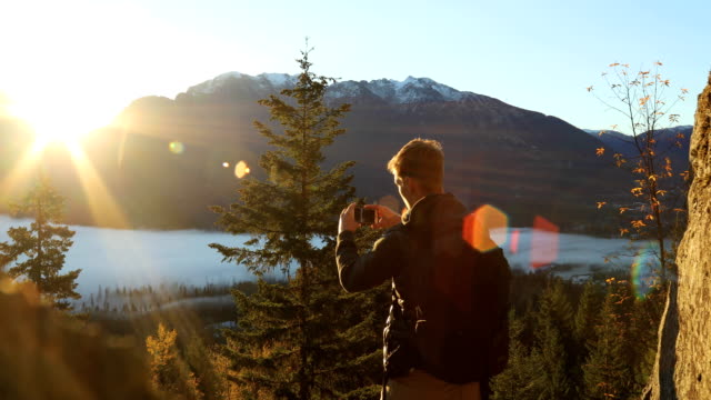 Hiker enjoys sunrise view of distant snowy mountains