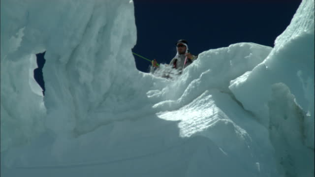 a hiker examines a huge crevasse in the snow. - crevasse stock videos & royalty-free footage