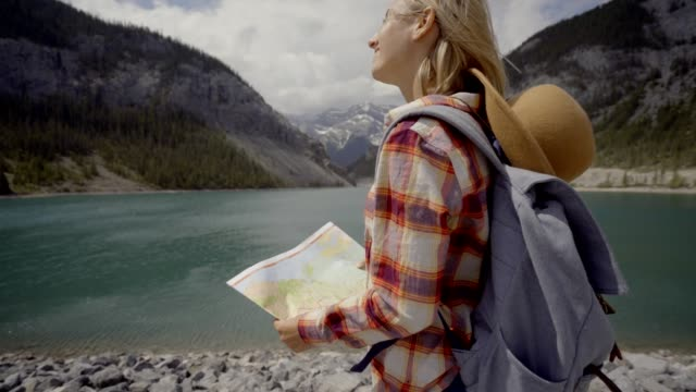 Hiker female looking at map near mountain lake