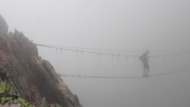 hiker follows suspension bridge into mist, on via ferrata route - exploration video stock e b–roll