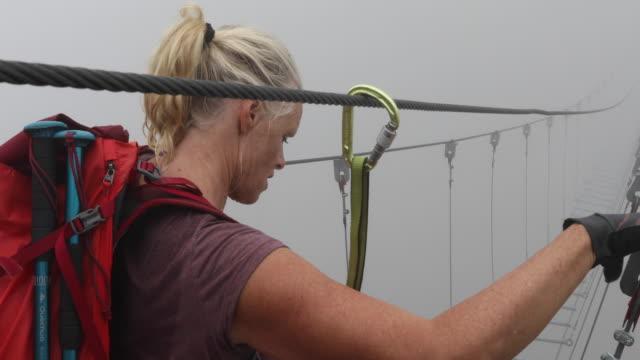 vídeos de stock e filmes b-roll de hiker follows suspension bridge into mist, on via ferrata route - corda
