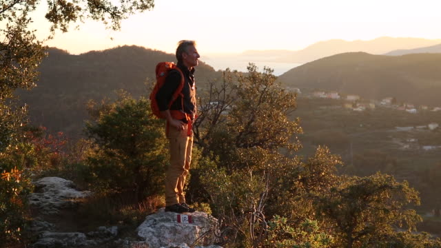 Hiker follows trail to promontory, looks out over hills at sunrise