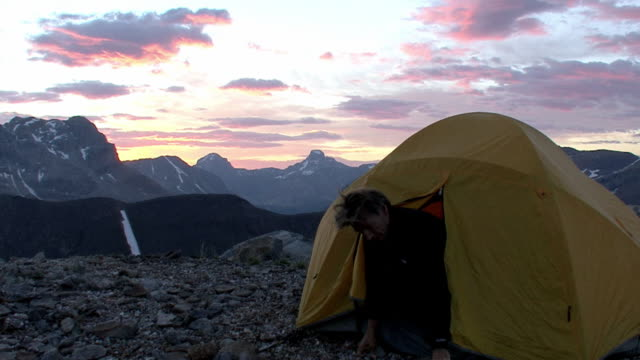 ws, hiker getting out from tent in mountains at sunrise, banff national park, alberta, canada - tent stock videos & royalty-free footage